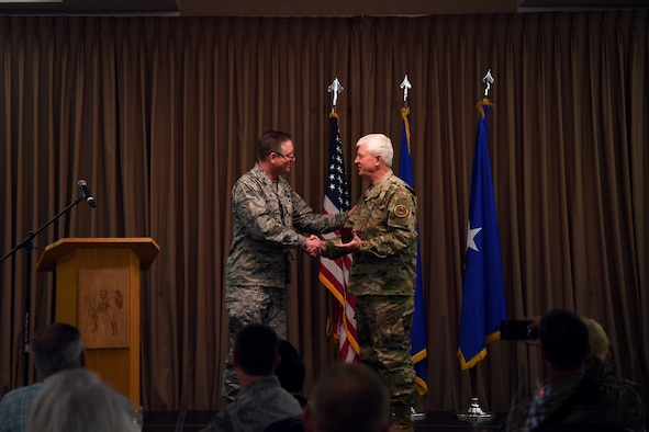 Ch. (Brig. Gen.) Ronald Harvell, Air Force Deputy Chief of Chaplains, accepts a memoir from Col. Benjamin Spencer, 319th Air Base Wing commander, during a National Day of Prayer luncheon on Grand Forks Air Force Base, North Dakota. Airmen, family members and community guests attended the luncheon, at which Harvell spoke about how to pray for the military. (U.S. Air Force photo by Senior Airman Elora J. Martinez)