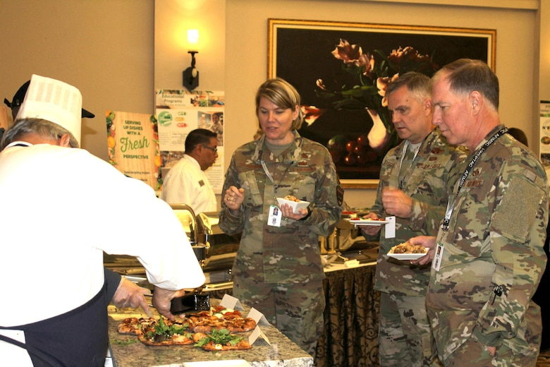 Attendees at the General Officer and Senior Executive Service Summit wait to be served fresh barbecue chik-n-less chicken pizza during lunch April 10, 2019, at Joint Base San Antonio-Lackland. AFSVA prepared various healthy and nutritious food items to familiarize summit attendees with Healthy Food Initiative, a dining concept being rolled out across the Air Force that's designed to deliver fresh, healthy, nutritious and tasty food to Airmen. (U.S. Air Force photo by Debbie Aragon)