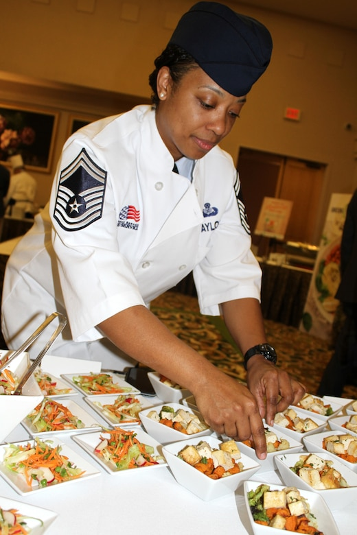 Senior Master Sgt. Tashon Taylor, AFSVA Food and Beverage superintendent, positions grain bowls with grilled tofu for a Healthy Food Initiative lunch during the General Officer and Senior Executive Service Summit April 10, 2019, at Joint Base San Antonio-Lackland. AFSVA prepared various healthy and nutritious food items to familiarize summit attendees with Healthy Food Initiative, a dining concept being rolled out across the Air Force that's designed to deliver fresh, healthy, nutritious and tasty food to Airmen. (U.S. Air Force photo by Debbie Aragon)