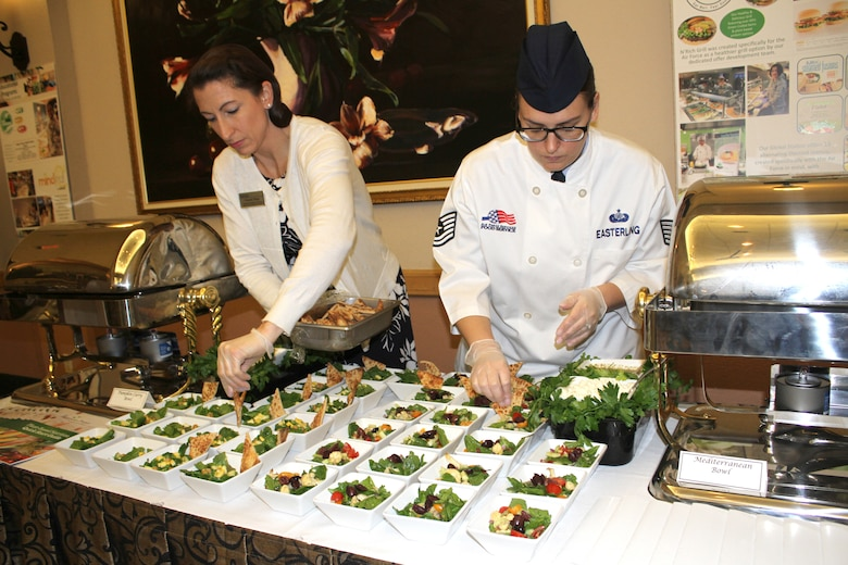 Christie Maas and Tech. Sgt. Audrey Easterling, food and beverage managers at the Air Force Services Activity, put the finishing touches on pumpkin curry and Mediterranean bowls for a Healthy Food Initiative lunch during the General Officer and Senior Executive Service Summit April 10, 2019, at Joint Base San Antonio-Lackland. AFSVA prepared various healthy and nutritious food items to familiarize summit attendees with HFI, a dining concept being rolled out across the Air Force. (U.S. Air Force photo by Debbie Aragon)
