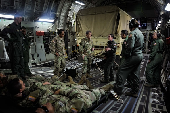 U.S. Air Force Maj. Gen. Randall A. Ogden, Fourth Air Force commanding officer, center, learns about the aeromedical evacuation mission from airmen assigned to the 452nd Aeromedical Evacuation Squadron, March Air Reserve Base, aboard a C-17 Globemaster III during exercise Patriot Hook, April 14, 2019, Naval Air Station North Island, California.