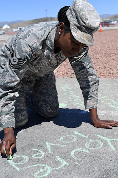 "Tech. Sgt. Janai, 799th Air Base Squadron personnelist, participates in a ""Chalk The Walk"" event to raise awareness of sexual assault and child abuse at Creech Air Force Base, Nevada, April 23, 2019. More than 150 Airmen attended the event, which included a barbecue and information booths manned by members of the Nellis AFB Sexual Assault Prevention and Response office and Mental Health. (U.S. Air Force photo by Master Sgt. Dillon White)"