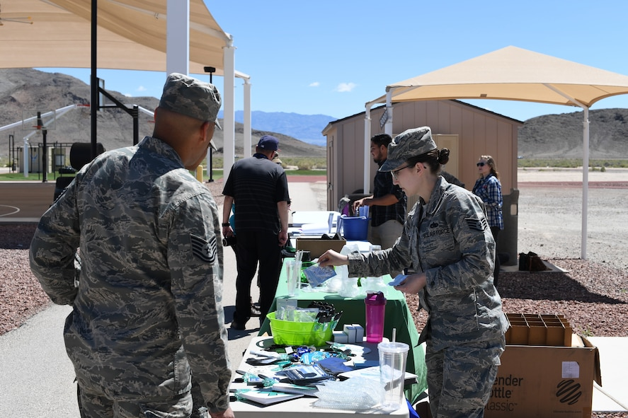 Staff Sgt. Alexis Johnson, Nellis Air Force Base Sexual Assault Prevention and Response volunteer victim advocate, shares information and promotional items with Airmen at Creech AFB, Nevada, April 23, 2019. Because April is Sexual Assault Awareness and Prevention and Child Abuse Prevention Month, helping agencies from Creech and Nellis spent the day informing Airmen and families about what programs are available to raise awareness and help victims of sexual assault and child abuse. (U.S. Air Force photo by Master Sgt. Dillon White)