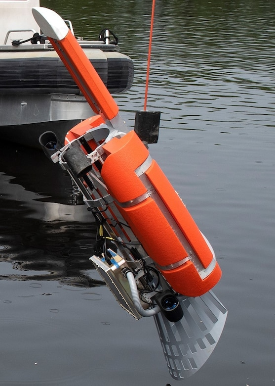 An unmanned underwater vehicle device is lowered into the water.