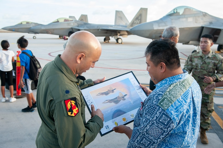 U.S. Air Force Lt. Col. Shane Nagatani, 199th Fighter Squadron commander, presents Ralph Torres, Governor of Saipan, a framed picture at the Francisco C. Ada International Airport, Saipan, April 23, 2019.