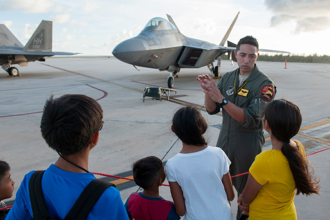 A 199th Fighter Squadron pilot from the Hawaii Air National Guard answers questions about the F-22 Raptor during a static display tour at the Francisco C. Ada International Airport, Saipan, April 23, 2019.