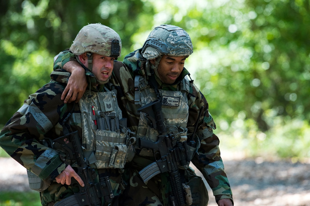 An Airman assists wounded personnel to a Humvee after responding to a simulated ground attack during exercise