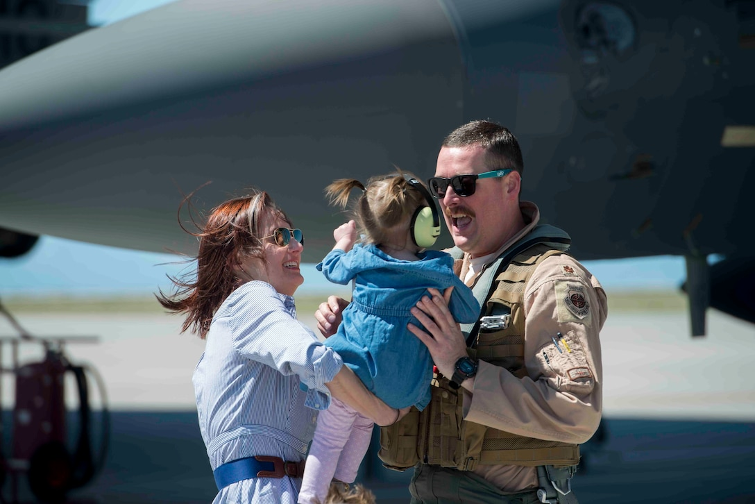 An Airman hugs his family as he returns from a six-month deployment