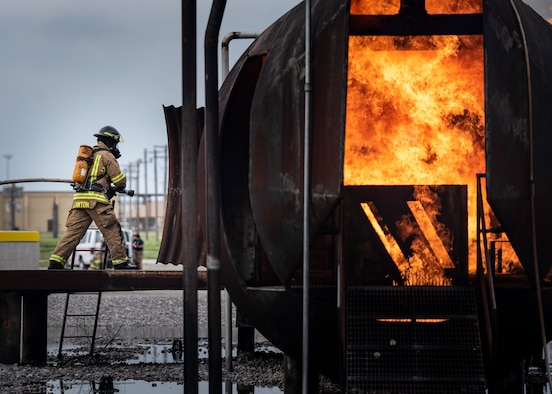 A firefighter gets in position to battle a simulated fire during a training exercise