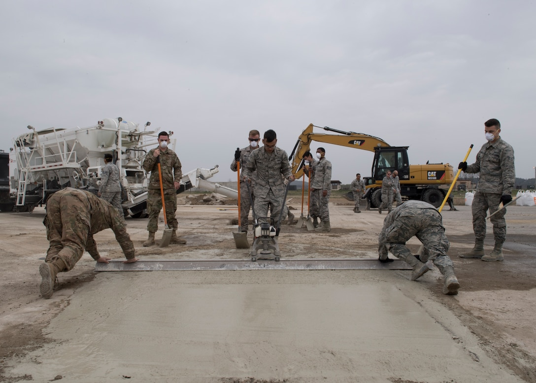 An Airman pulls a vibrating screed during rapid airfield damage repair training