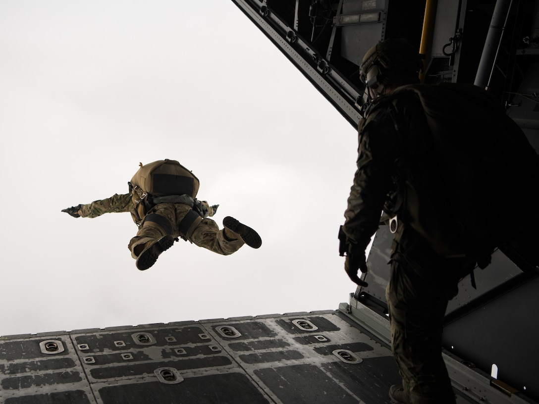 A special tactics operator jumps out of the back of an MC-130H