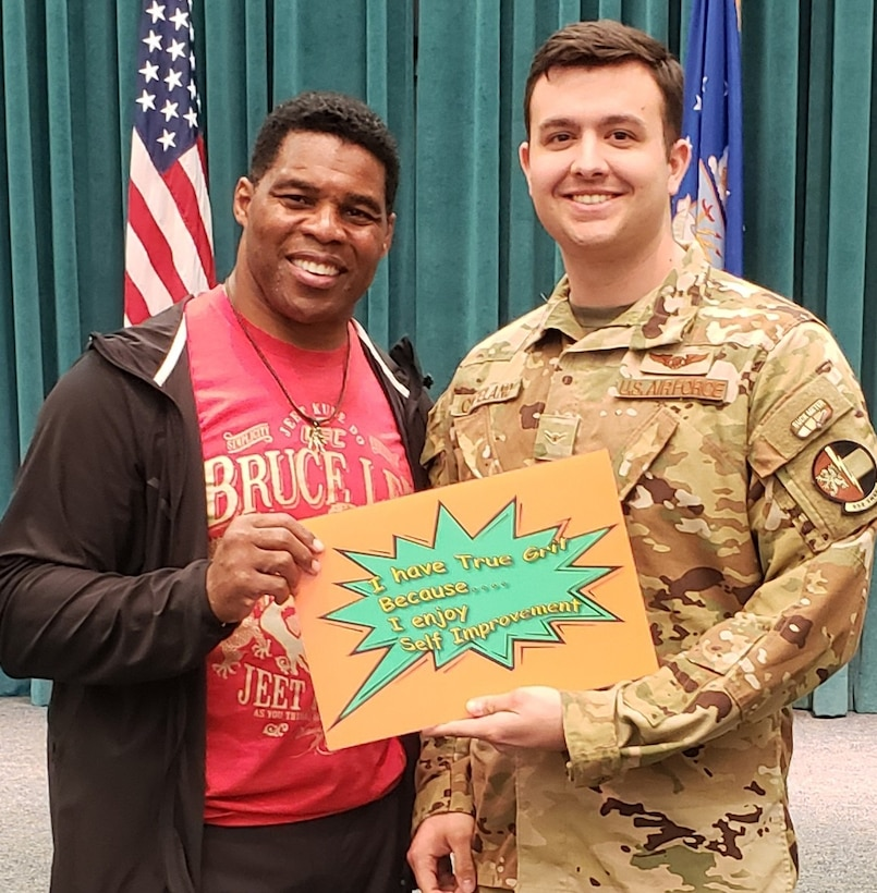 Former NFL Star and Heisman Trophy winner Herschel Walker kicked off the True Grit campaign when he visited Tinker on March 25 to talk to the Oklahoma City Air Logistics Complex, 552nd Air Control Wing and the 72nd Air Base Wing about the grit that it took to overcome his personal obstacles. Walker is pictured with Airman 1st Class Gregory Copeland of the 963rd Airborne Air Control Squadron with a painting of how true grit is exemplified to him, self improvement. (Courtesy photo)