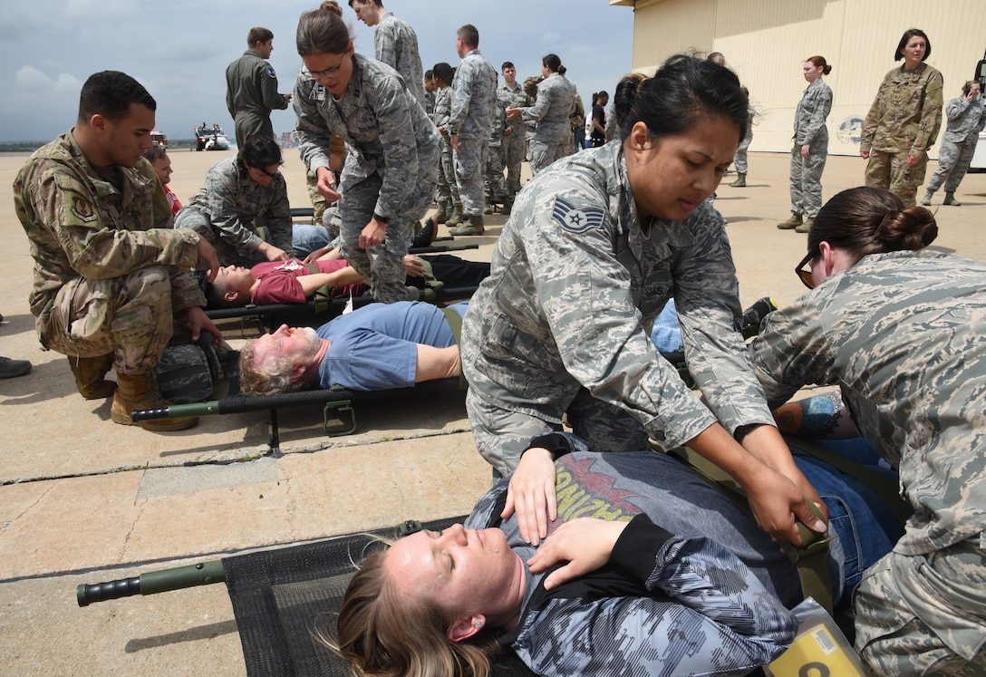Personnel with the 72nd Medical Group respond to injured bystanders during an airshow exercise Apr. 17. The bystanders were all volunteers from various Tinker units who were given specific injuries that were made more realistic by moulage artwork. By making an exercise scenario more realistic, it helps first responders train and prepare for real-world situations. (U.S. Air Force photo/Kelly White)