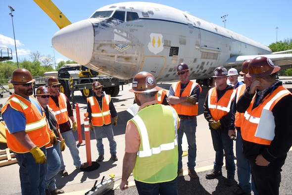 Josh Harvey, crash damaged disabled aircraft recovery (CDDAR) team chief, gives a safety briefing to his team after all of the equipment has been set up and before they lift the aircraft. During this simulated event, the team was given the scenario that the aircraft's front landing gear had collapsed and they would need to simulate a nose lift with a crane to then tow to a repair facility. Due to high winds Apr. 18, they could only simulate the lift due to safety reasons. (U.S. Air Force photo/Kelly White)