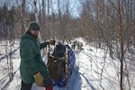 Geoffrey Dominessy, a contracting officer, in the Defense Logistics Agency Troop Support's Construction and Equipment supply chain, stands next to his dog sled during a trip hosted by Outward Bound for Veterans in February 2019 in Northern Minnesota.