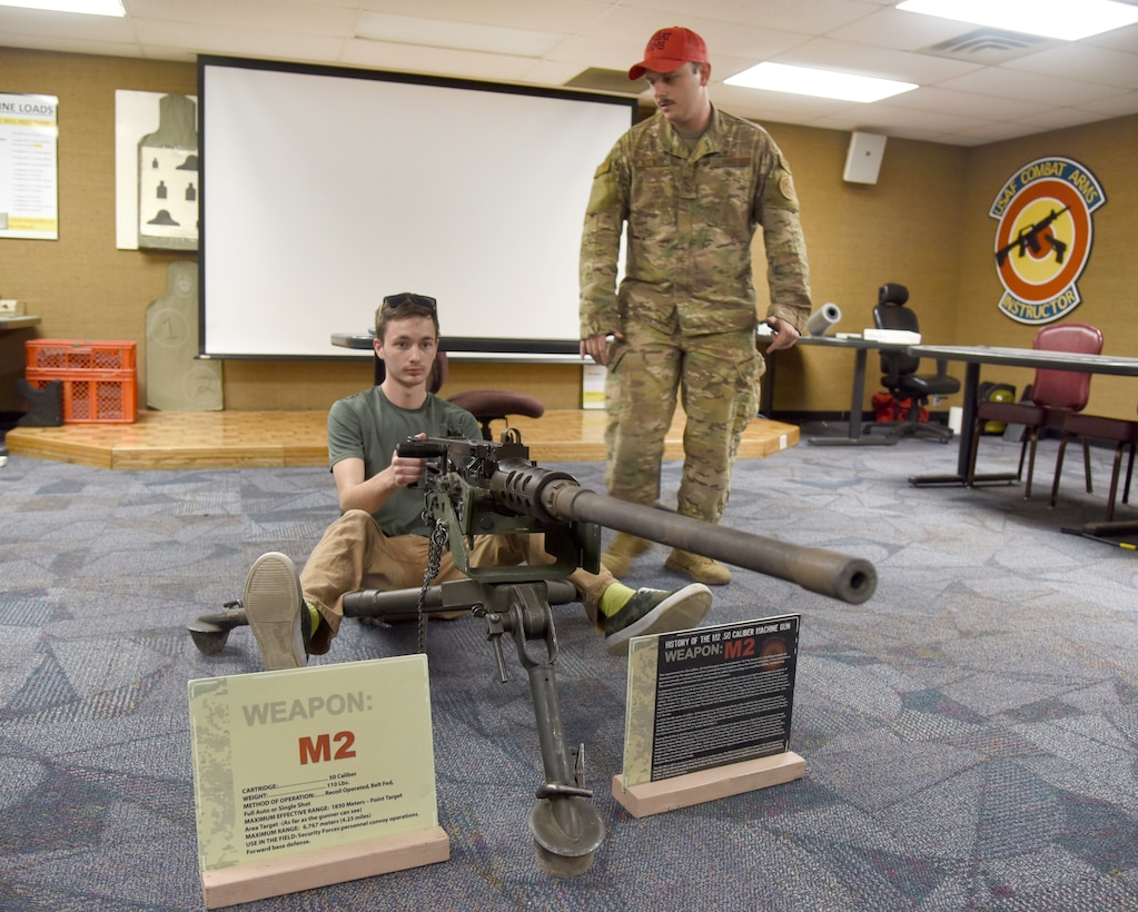 Staff Sgt. Justin Piercefield, 72nd Security Forces Combat Arms instructor, shows Air Force recruit Levi Maxwell how to properly position himself on the M2 machine gun during a weapons display portion of the Delayed Enlistment Program Call Apr. 8. The 72nd SFS worked with the 349th Recruiting Squadron to have 15 recruits learn more about the security forces career field. The military working dogs section, investigations, combat arms and training sections demonstrated their respective areas during the event, giving the recruits, some of whom haven't yet selected a career field, a better insight into this one.