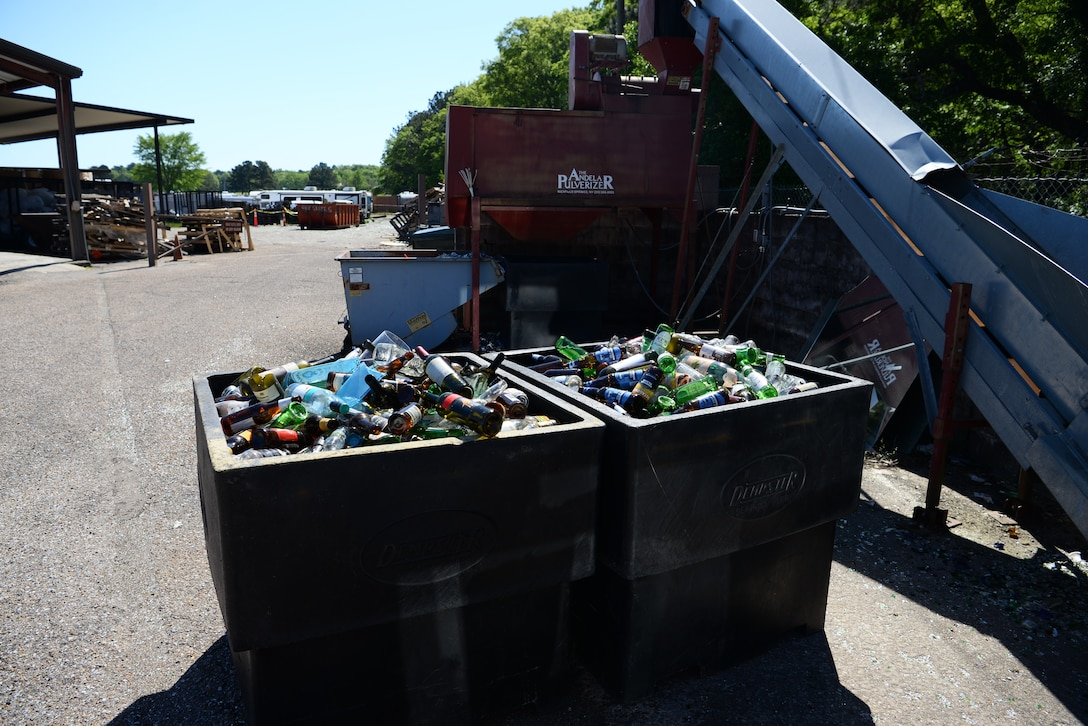 Bins full of glass next to a pulverizing machine, April 22, 2019, on Columbus Air Force Base, Miss. Once enough glass is collected at the recycling center, it is thrown into the machine and turned into sand and potting soil by pulverizing it down. (U.S. Air Force photo by Airman 1st Class Jake Jacobsen)