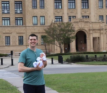 Air Force Capt. (Dr.) Andy Murtha holds baby Claire in front of the old Brooke Army Medical Center building at Joint Base San Antonio-Fort Sam Houston April 6, 2019. Murtha and his daughter share the legacy of being born at BAMC.