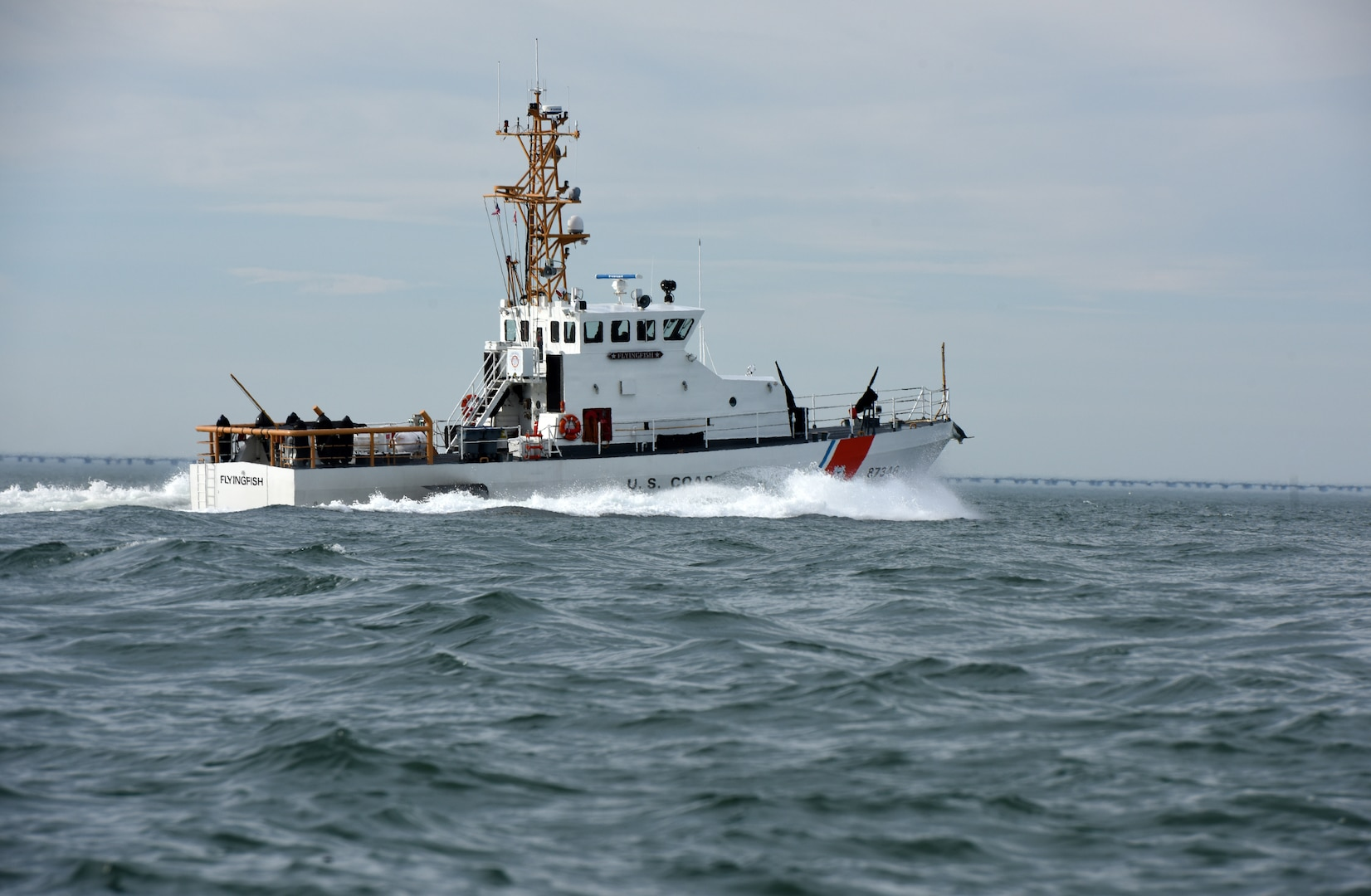 Coast Guard Cutter Flying Fish, an 87-foot patrol boat homeported in Virginia Beach, Virginia, steams north alongside the Chesapeake Bay Bridge-Tunnel off Virginia Beach, Feb. 15, 2018. The cutter's crew of 12 primarily conducts search and rescue and marine fisheries enforcement missions in the lower Chesapeake Bay and off Virginia's coast.