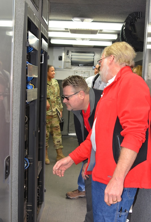 Mark McKay (center) and Howard Bulick (right), both from the Portland District, examine some of the equipment in an ECCV during the exercise, April 17, 2019.