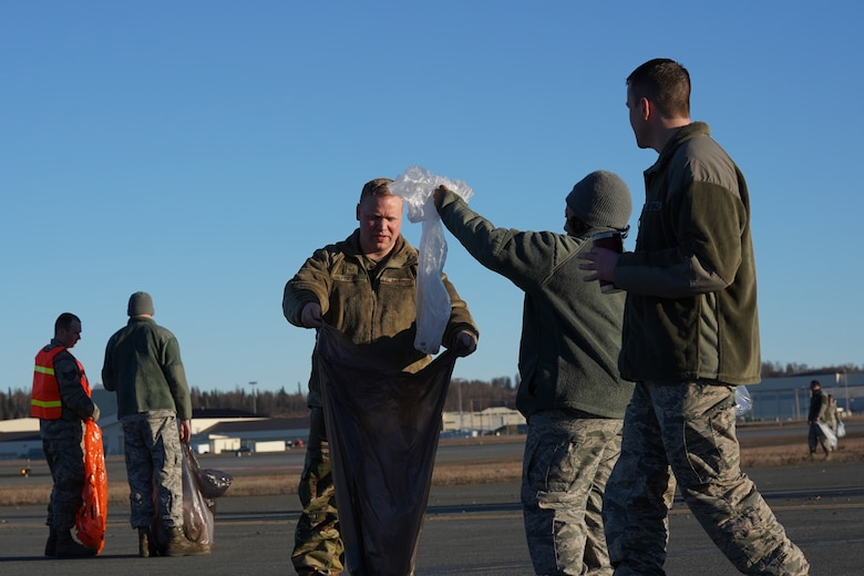 U.S. Airmen from the 3rd Wing, 176th Wing, and 477th Fighter Group conduct a foreign object debris walk on the flightline at Joint Base Elmendorf-Richardson, Alaska, April 26, 2019. The Airmen conducted the FOD walk to remove debris that could damage aircraft and hinder mission readiness.