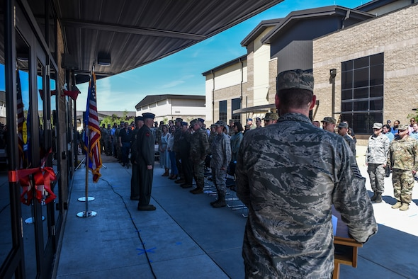 Col. Spencer Thomas, vice commander, left, and Lt. Col. Jason Bialon, 427th Reconnaissance Squadron commander, stand at attention during the opening ceremony for the ribbon cutting of the Common Mission Control Center at Beale Air Force Base, California, April 23, 2019. The CMCC provides products, services, more advanced and inclusive than any legacy Theater Air Control System element. (U.S. Air Force Photo by Senior Airman Colville McFee)