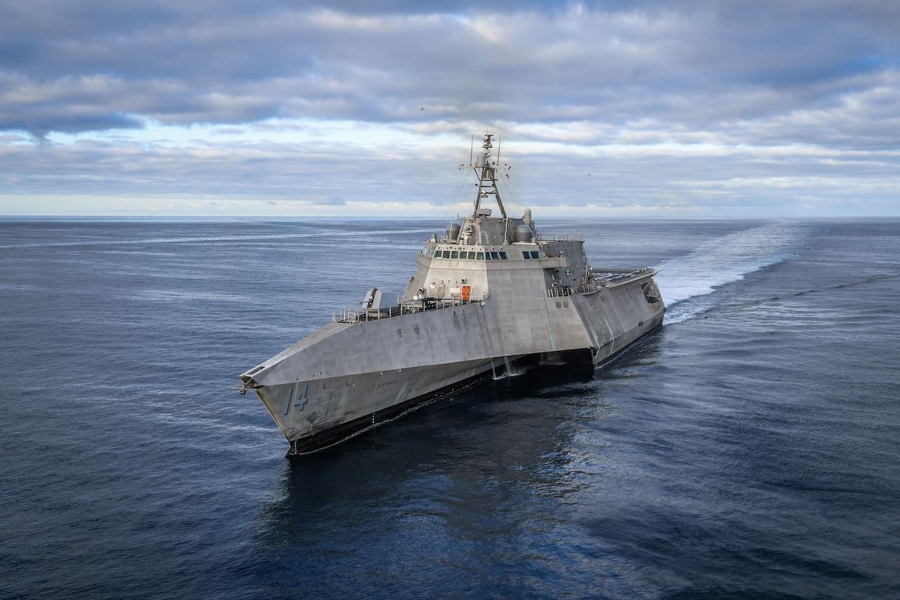 A military ship moves through the ocean.