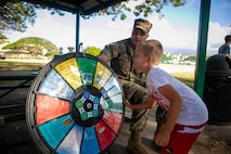U.S. Marine Corps Cpl. Larry Hunter, an energy noncommissioned officer with Headquarters Battalion, Marine Corps Base Hawaii (MCBH), monitors as a child spins a questionnaire spin wheel during an environmental Earth Day event, Risely Field, Apr. 23, 2019. The annual event was held to inform residents of MCBH about the importance of energy conservation, recycling, and the various methods of keeping the environment clean and pollution free. (U.S. Marine Corps photo by Sgt. Zachary Orr)