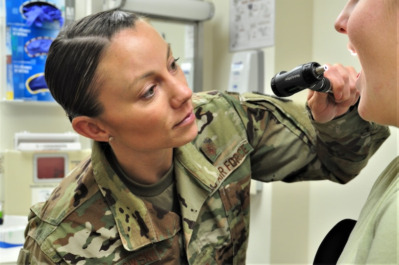 U.S. Air Force Capt. Shauna Sokolowski, 359th Medical Group Family Health clinical nurse, checks the inside of a simulated patient's mouth at Joint Base San Antonio-Randolph, Texas, April 23, 2019. National Nurses Week takes place May 6-12, Florence Nightingale's birthday. (U.S. Air Force photo by Tech. Sgt. Ave I. Young)