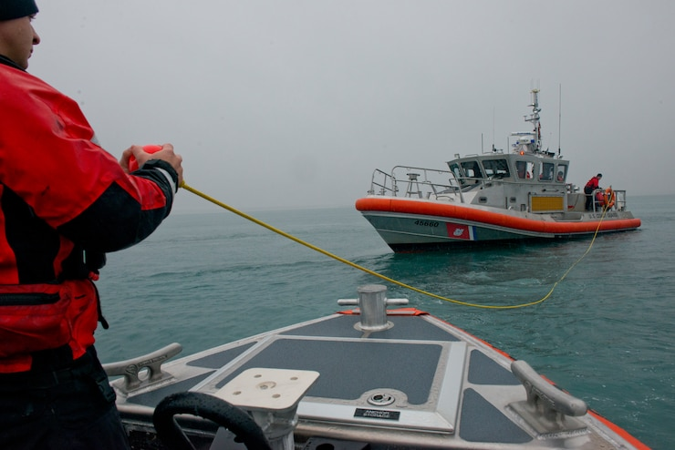 Coast Guard Petty Officer 3rd Class Alex Sheltra prepares to haul aboard a tow line after receiving a heaving line from a 45-foot Response Boat-Medium crew in the Port of Valdez, Alaska, Oct. 10, 2018. The  Station Valdez crews conducted training that included search patterns and vessel towing.