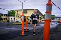 A child sprints to the finish line during the Keiki Koa Kai Sprint Triathlon, Marine Corps Base Hawaii, Apr. 27, 2019. The swim, bike, run triathlon is an annual event held aboard the base for children ages 7 to 14 and is part of the Commanding Officer's Fitness Series composing of 11 races throughout the year.. (U.S. Marine Corps photo by Cpl. Matthew Kirk)