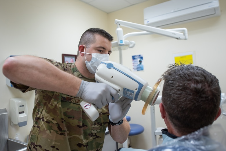U.S. Air Force Staff Sgt. Garrett Weston, 380th Expeditionary Medical Group dental element noncommissioned officer-in-charge, X-rays a patient's teeth at Al Dhafra Air Base, United Arab Emirates, April 23, 2019. Garrett is deployed with his brother U.S. Air Force Staff Sgt. Cameron Weston, 380th Expeditionary Aircraft Maintenance Squadron F-35 Lightning II Egress technician. (U.S. Air Force photo by Staff Sgt. Chris Thornbury)