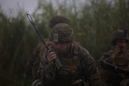 A Marine with Charlie Company, Battalion Landing Team, 1st Battalion, 4th Marines, speaks into a handheld radio during a simulated helicopter raid as part of the 31st Marine Expeditionary Unit's MEU Exercise at Ie Shima Training Facility, Okinawa, Japan, Dec. 11, 2018. BLT 1/4 is the Ground Combat Element for the 31st MEU. MEUEX is the first in a series of pre-deployment training events that prepare the 31st MEU to deploy at a moment's notice. The 31st MEU, the Marine Corps' only continuously forward-deployed MEU, provides a flexible force ready to perform a wide-range of military operations across the Indo-Pacific region.