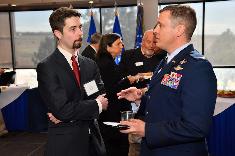 Col. Jack Fischer, 50th Space Wing vice commander, speaks with Corbin Hart City of Fountain economic developer, during the annual State of the Base at Schriever Air Force Base, Colorado, April 25, 2019. State of the Base provides leaders opportunity to engage community members about Schriever's mission and vision, and partnership opportunities. (U.S. Air Force photo by Kathryn Calvert)