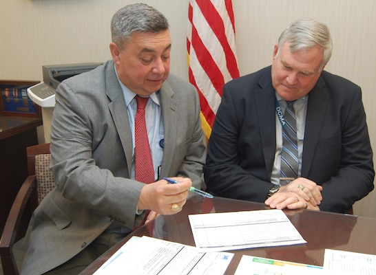 Two men wearing business suits sit at a table discussing a briefing