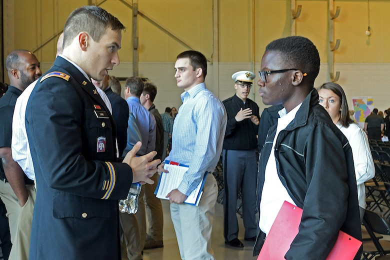 A United States Military Academy representative talks with a high school student about what it is like to attend a military academy at Dobbins Air Reserve Base, Ga. on April 27, 2019. Dobbins hosted the 20th annual Academy Day, where representatives from all the military service academies come to talk with potential attendees, and students come to meet congressional representatives (U.S. Air Force photo by Tech. Sgt.  Miles Wilson).