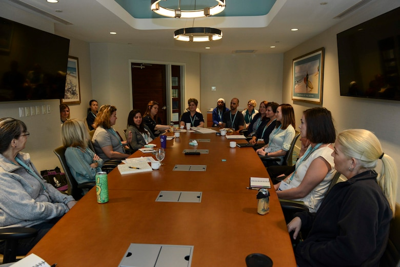 A group of people sitting at a conference table in a conference room.