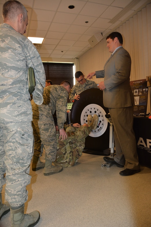 J.D. Bales, of the Air Force Research Laboratory, demonstrates the Air Force new C-5 tire changing tool to senior leaders from across the Air Force. The new tool requires two Airmen to change a tire with a tool adjustable in height and angle use on all tires with a faceplate designed for interoperability with all current spanner wrenches. The previous tool required five Airmen. The demo was part of an AFRL Tech Expo for the Basing and Logistics Board. (U.S. Air Force photo/Karen Schlesinger)