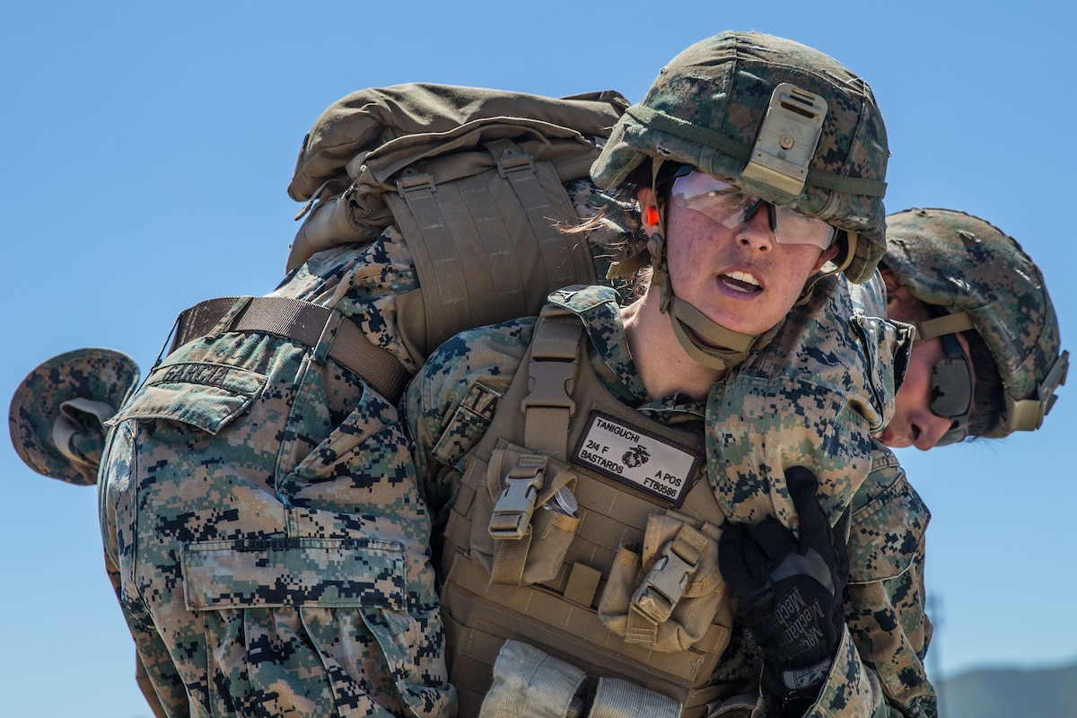 A Marine wearing protective lenses and a helmet carries another Marine across her shoulders.