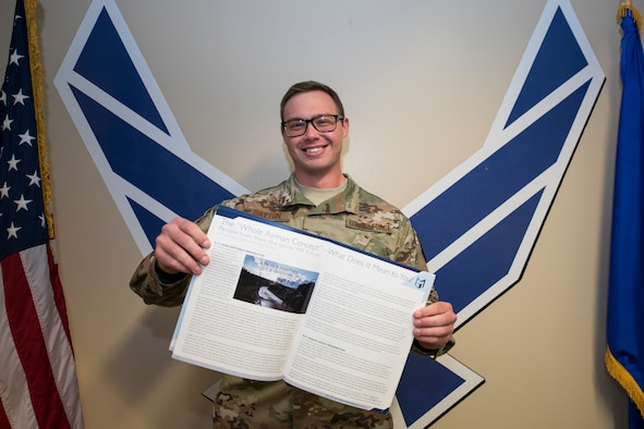 Airman 1st Class Chad Dayton, 27th Special Operations Comptroller Squadron financial operations technician, holds open a printed copy of the article he wrote for a comptroller magazine at Cannon Air Force Base, N.M., Apr. 23, 2019. Dayton received the Special Operations Command Financial Management Outstanding Author Award for the article