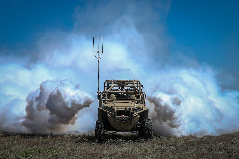 Clouds of vapor surround the sides and rear of a vehicle in a field.
