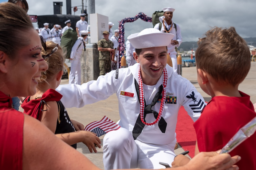 A Sailor assigned to the Los Angeles-Class fast-attack submarine USS Santa Fe (SSN 763) greets his family after he arrived at Joint Base Pearl Harbor-Hickam, after completing his latest deployment, April 22. (U.S. Navy Photo by Mass Communication Specialist 1st Class Daniel Hinton)