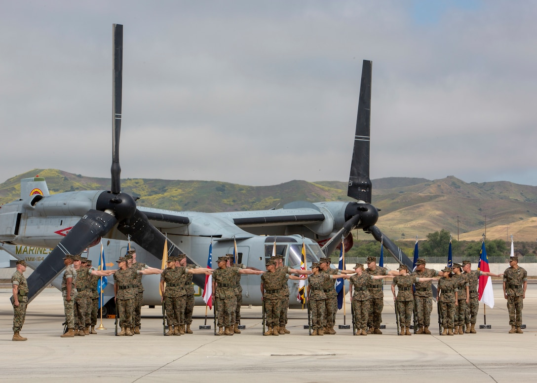 A group of Marines stand in rows in front of an aircraft.