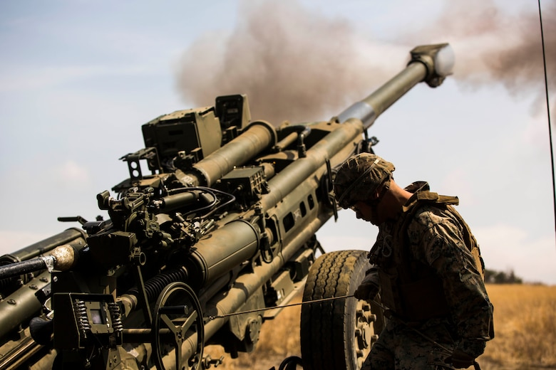 A Marine stands next to a large military gun that has smoke coming out from the top.
