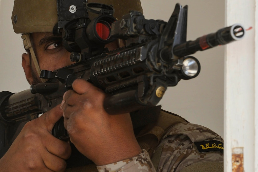 A service member looks through the scope on a rifle.