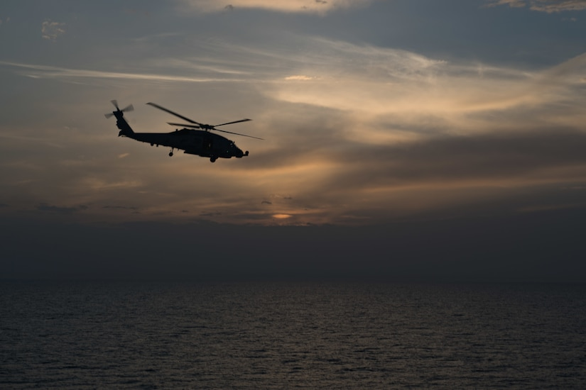A helicopter flies solo over the ocean.