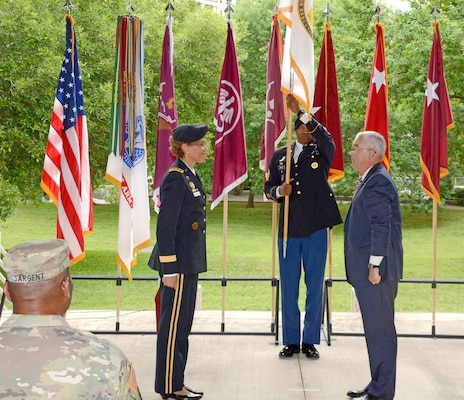 Command Sgt. Maj. Michael L. Gragg, MEDCOM Command Sergeant Major, unfurls the Senior Executive Service flag, as Lt. Gen. Nadja Y. West and Joseph M. Harmon III look on. Harmon was appointed to the Senior Executive Service in a ceremony at the Army Medical Department Museum April 29.