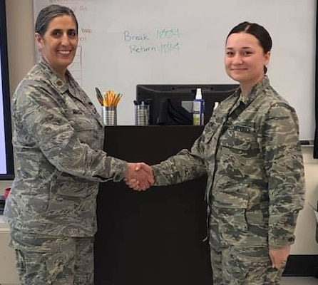 Maj. Brenda Miazga (left), Medical Education and Training Campus Aerospace Medical Service Apprentice program department chair, presents Airman Grace Dawson with a challenge coin for her actions during a medical emergency.