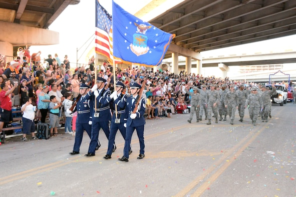 The 433rd Airlift Wing's Honor Guard leads the 433rd Airlift Wing and 960th Cyberspace Wing walkers and float on Broadway Street in downtown San Antonio during the 71st annual Fiesta Flambeau Parade, April 27, 2019.