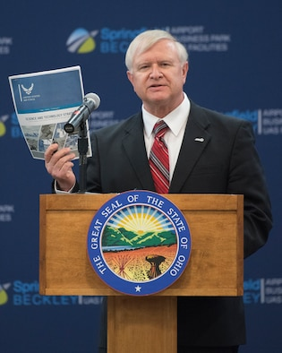 Jack Blackhurst, Air Force Research Laboratory executive director, holds up a copy of the U.S. Air Force Science and Technology Strategy, released by Secretary of the Air Force Heather Wilson, as he addresses the audience April 26, 2019, at the Springfield-Beckley Municipal Airport in Springfield, Ohio. The event was to announce the Federal Aviation Administration granting a Certificate of Waiver or Authorization to AFRL for beyond visual line of sight flights of unmanned aerial systems. (U.S. Air Force photo by R.J. Oriez)